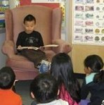 CHild reading to class mates